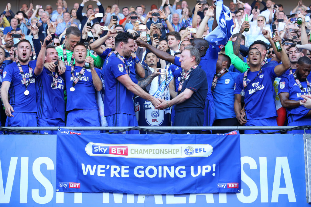 CARDIFF, WALES - MAY 06: Sean Morrison of Cardiff City and Cardiff City manager Neil Warnock shake hands as they lift the trophy after being automatically promoted to the Premier League after the final whistle of the Sky Bet Championship match between Cardiff City and Reading at The Cardiff City Stadium on May 06, 2018 in Cardiff, Wales. (Photo by Athena Pictures/Getty Images)